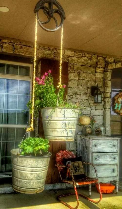De vieux seaux suspendus transformés en pots de fleurs